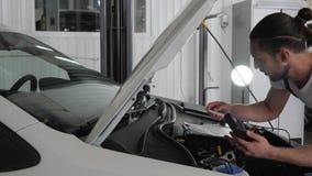 Specialistenmechanician de mens bevindt zich dichtbij open kap controleert bedradings automobiel systeem, Motoroverzicht, foutend stock footage