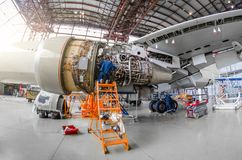 Specialistmekanikern reparerar underhållet av en stor motor av en passagerarflygplan i en hangar Sikt av motorn utan hättan, royaltyfria bilder