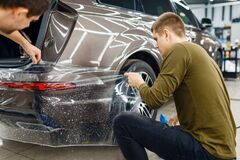 Specialists applies car protection film on bumper