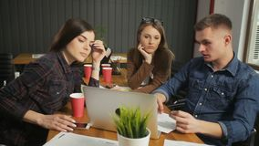 IT Specialists Discuss Concept. Fair-haired man in denim blue shirt informing female colleagues about main concept of the project, two attractive women sitting stock video