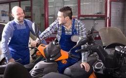 Specialists working with motocycles Royalty Free Stock Images