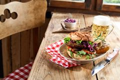 Speciality venison beef burger with frothy beer. Speciality venison beef burger on a crusty bun with frothy cold beer and potato edges for a rustic tavern lunch royalty free stock photo
