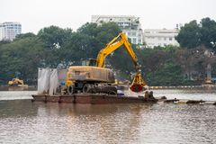 Specialized floating excavator cleans marine sediments of lake bottom.  stock image