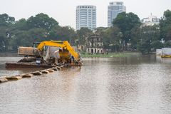 Specialized floating excavator cleans marine sediments of lake bottom.  stock photo