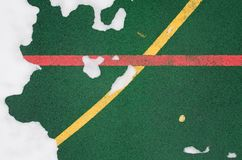 A specialized outdoor sports ground covering a rubber crumb of green color with marked lines for playing sports. Covered. A close-up is a specialized outdoor Royalty Free Stock Images