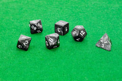 Specialized polyhedral dice for role-playing games on green clot. Set of specialized polyhedral dice with numbers used in role-playing games on a table with Royalty Free Stock Photos
