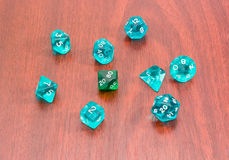 Specialized polyhedral dice for role-playing games on wooden sur. Set of blue and green specialized polyhedral dice with numbers used in role-playing games on a royalty free stock image