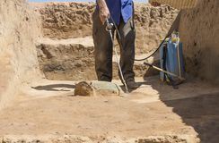 Specialized worker sprays an half-buried bronze piece at archaeological site. Guareña, Extremadura, Spain stock photos