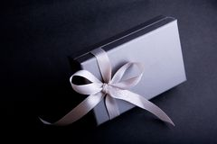 Specially Wrapped Gift Box. A view of a perfectly wrapped gift box with silver paper, a pink ribbon and beautiful bow stock photography