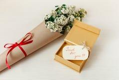 Specialt önskakort med den guld- närvarande asken med vita små blommor för bukett i brunt hantverkpapper Vit trätexturbakgrund Royaltyfri Bild