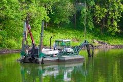 Specialt skepp, arbetsplattform som är i bruk på ett litet damm Röjningflodbäddar och lokalvård av dammbotten Royaltyfria Bilder