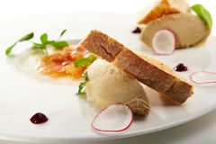 Specialties of the luxury restaurant. Pate of fowl with toast and citrus jam with radish slices and fresh herbs on flat white plate. Gastronomic restaurant menu Royalty Free Stock Photography