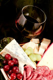 Specialty cheese. With salami and grapes Royalty Free Stock Photos