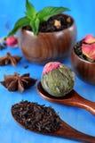 Specie nere e verdi del fiore, di tè in tazze e cucchiai di legno fotografia stock libera da diritti
