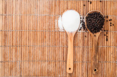 Species in two wooden spoon on bamboo table Royalty Free Stock Photos