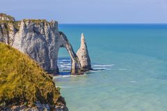 Cliffs of Etretat, Normandy,France. Specific cliffs in Etretat in the Upper-Normandy region in Northern France at low tide: the needle rock and the stone arch Royalty Free Stock Photo