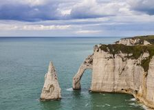 Cliffs of Etretat, Normandy,France. Specific cliffs in Etretat in the Upper-Normandy region in Northern France at low tide: the needle rock and the stone arch Stock Photography