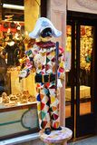 Specific Venetian mannequin. Venetian mannequin standing in front of the shop entrance, wearing the specific Venetian mask and carnaval clothing Royalty Free Stock Photo