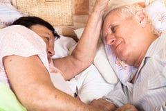 Två pensionärer kopplar av i säng Arkivfoto