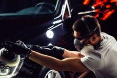 Specificera för bil - mannen med orbitalpolisheren i auto reparation shoppar Selektivt fokusera Royaltyfri Bild