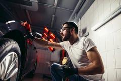 Specificera för bil - mannen rymmer microfiberen i hand och polerar bilen royaltyfria foton
