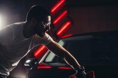 Specificera för bil - mannen rymmer microfiberen i hand och polerar bilen Royaltyfri Fotografi