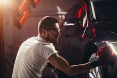 Specificera för bil - mannen rymmer microfiberen i hand och polerar bilen Arkivfoton