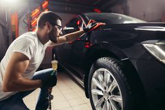 Specificera för bil - mannen rymmer microfiberen i hand och polerar bilen arkivfoto