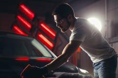 Specificera för bil - mannen rymmer microfiberen i hand och polerar bilen royaltyfria bilder