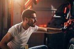 Specificera för bil - mannen rymmer microfiberen i hand och polerar bilen fotografering för bildbyråer