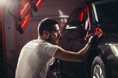 Specificera för bil - mannen rymmer microfiberen i hand och polerar bilen arkivbild