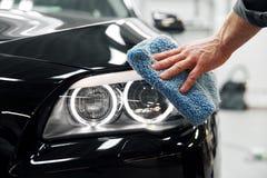 Specificera för bil - mannen rymmer microfiberen i hand och polerar bilen royaltyfri bild