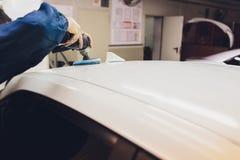 Specificera f?r bil - h?nder med orbitalpolisheren i auto reparation shoppar Selektivt fokusera arkivbilder