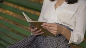specificera Kvinnliga händer med en bok Flickan på en bänk i hösten parkerar läser en grön bok 4K arkivfilmer