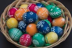 Specificerad makro som skjutas av handpainted färgrika easter ägg i ett dekorativt rede royaltyfria foton