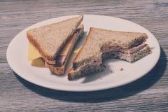 Specificerat siktsfoto för slut upp av den smakliga smaskiga bet hemlagade smörgåsen på vitrundaplattan Smaklig biten skinksmörgå royaltyfri fotografi