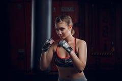 Specifieke jonge vrouwelijke vechter die een vlaag van stempels op het zware onduidelijke beeld van de zakmotie op haar handen we stock foto