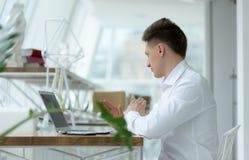 Specifieke modieuze jonge zakenman die project via boodschapper in comfortabele kleine koffie bespreken stock fotografie
