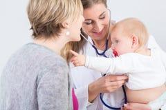 Specifieke vrouwelijke arts die een leuk babymeisje in haar wapens houden royalty-vrije stock afbeeldingen