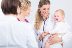 Specifieke vrouwelijke arts die een leuk babymeisje in haar wapens houden stock foto's
