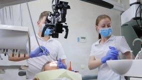 Specjalista i pomocniczego use okulistyczny mikroskop prowadzić operację z w usta łgarski pacjent w stomatologicznym pokoju zdjęcie wideo