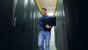 IT specjalista z laptopem obserwuje serwerów bloki Serweru inżynier Pracuje przy Data Center zdjęcie wideo