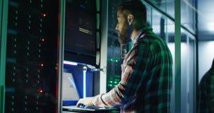 IT specjalisty mówienie na telefonie podczas gdy pracujący w serweru pokoju zbiory