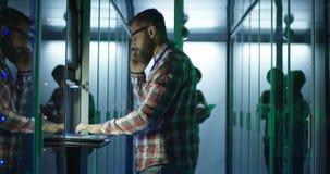 IT specjalisty mówienie na telefonie podczas gdy pracujący w serweru pokoju zbiory wideo