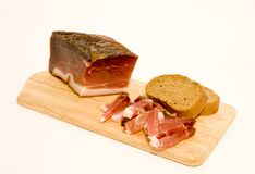 Speck and bread. A plate of speck with bread, placed over white background Stock Photos