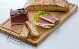 Speck ham and bread. On the cutting board stock photos