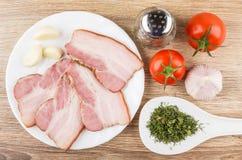 Speck mit Knoblauch in der Platte Pfeffer, Tomaten und Grüns Stockfotos