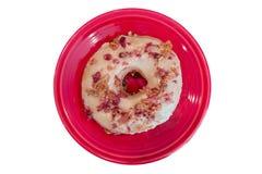 Speck-und Ahorn-Donut auf roter Platte Stockfotos