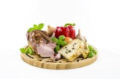 Speck und Brot mit Gemüse auf hölzernem Brett Stockfoto