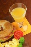 Speck- und Käsebagel mit durcheinandergemischten Eiern und Saft Lizenzfreies Stockfoto